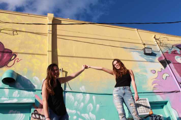photo of two laughing women holding hand while standing near graffiti wall