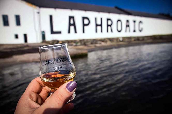 A Laphroaig dram in front of the Islay distillery
