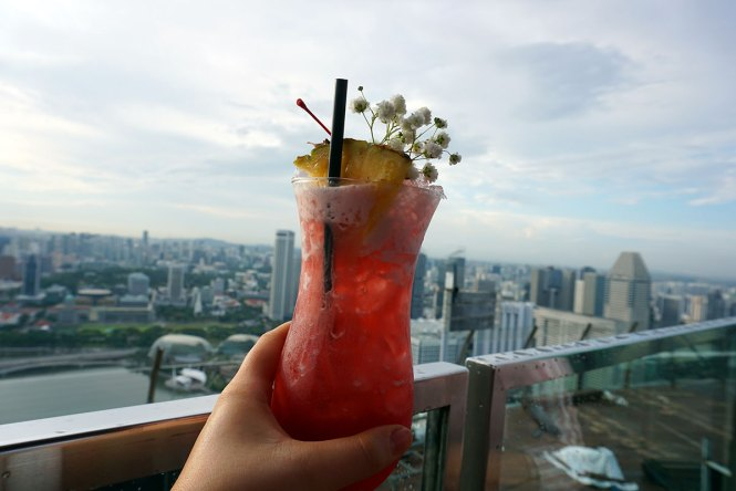 Singapore Sling cocktail in front of city skyline