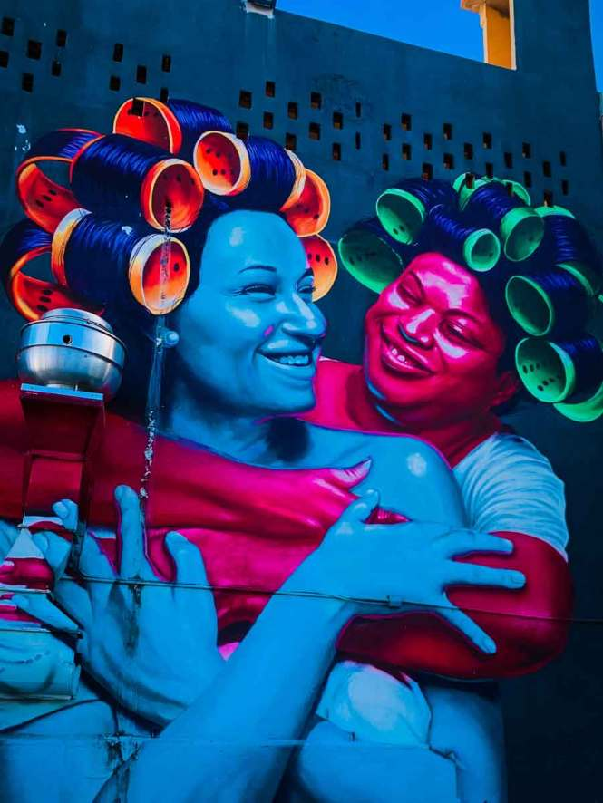 mural of two women with their hair in rollers hugging