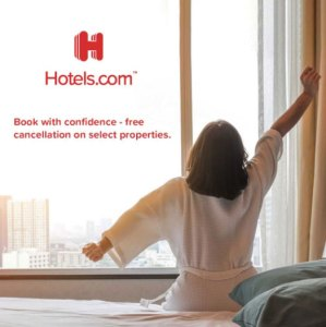 Hotels.com free cancellation banner with woman stretching on hotel bed with view of city