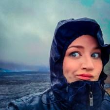Jordan looking over her should at a live volcano in Iceland, link in bio header image