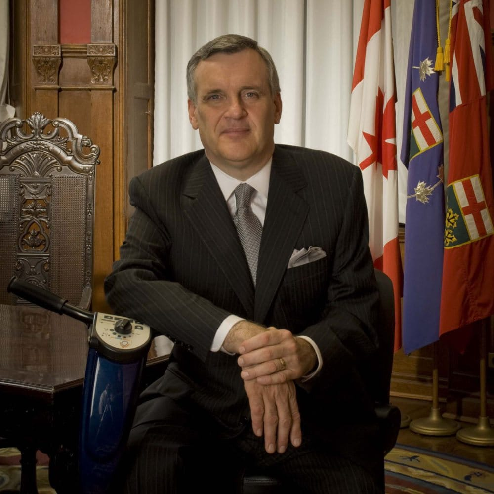 Pictured is a white man with clean cut grey hair, wearing a business suit and tie, sitting on a mobility device, in front of Canadian and provincial flags.