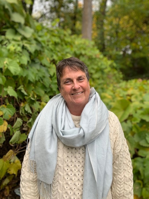 A photo of a middle-aged woman with short brown hair, and with gray at the temples. She is smiling at the camera with her head tilted to one side. She wears a cream-coloured, cable-knit sweater with a pale blue scarf around her neck. She stands in front of green vines in a woodland.
