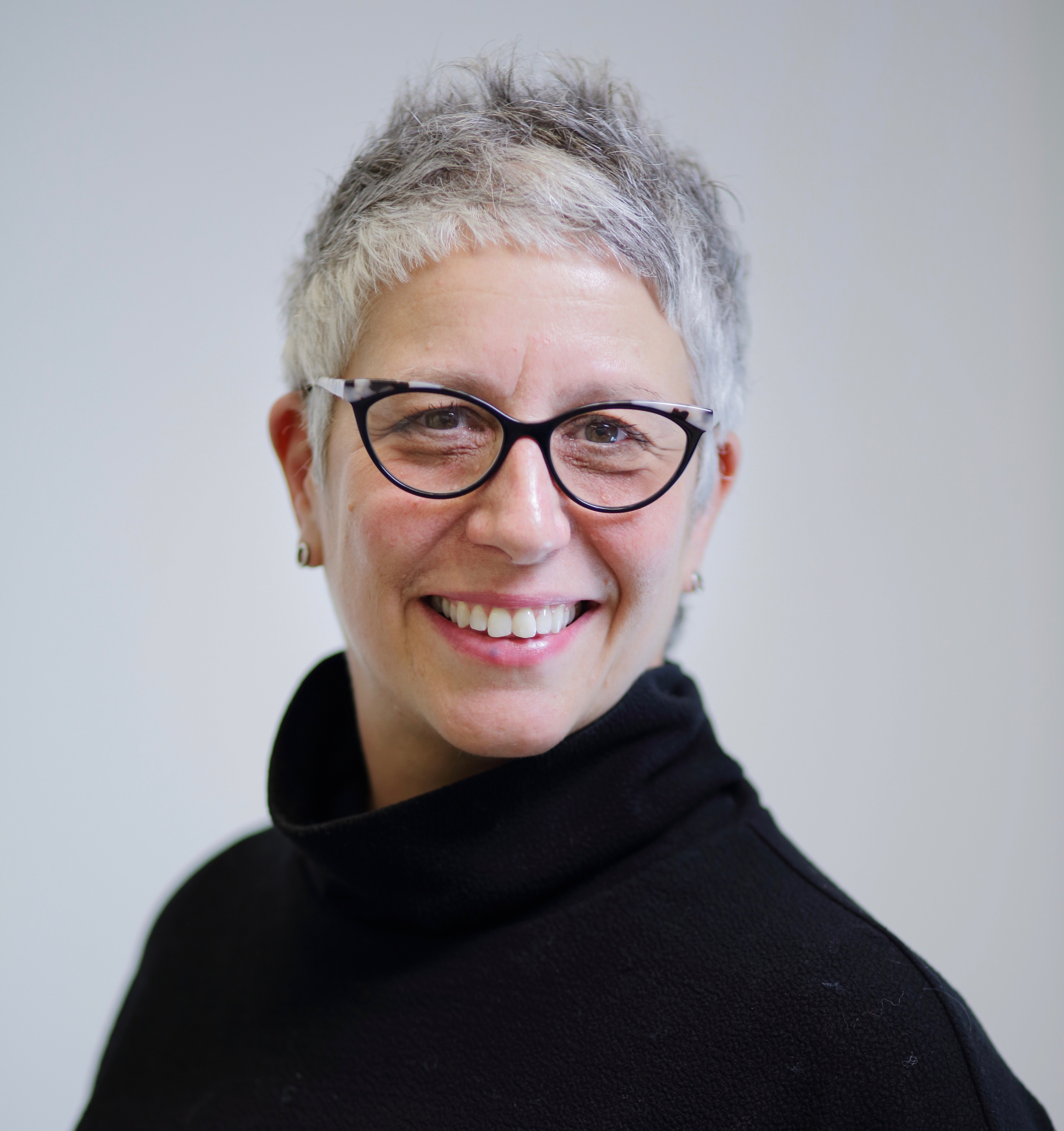a light-skinned person with short gray hair and black and tortoise-shell cat-eye glasses looks at the camera over her left shoulder. She is smiling with light pink lips and her teeth showing. Her face is lightly wrinkled with brow lines and laugh lines. She wears a black turtleneck and small silver earrings