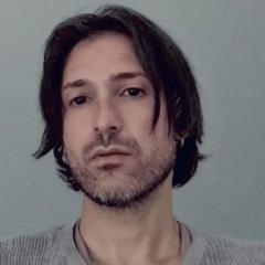 Colour headshot of a white male with dark, medium-to-long hair, and facial hair