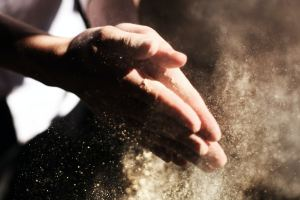 person clapping its hand with sand