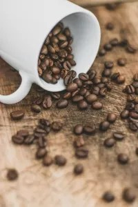 white ceramic mug on brown coffee beans