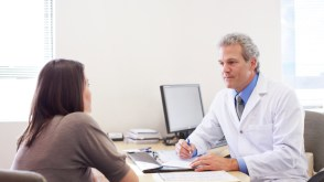 A mature doctor sitting behind his desk having a discussion with his female patient