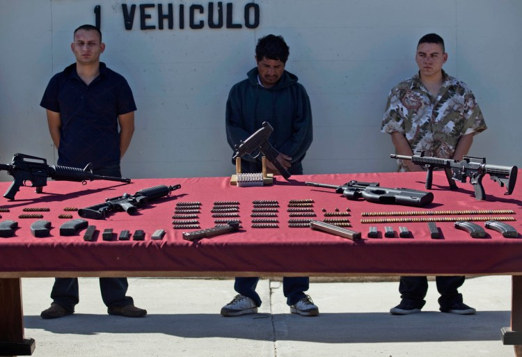 Suspected members of the Arellano Felix drug cartel, stand next to displayed weapons during a presentation to the media in Tijuana, Mexico, March 15, 2010. (AP Photo/Guillermo Arias)