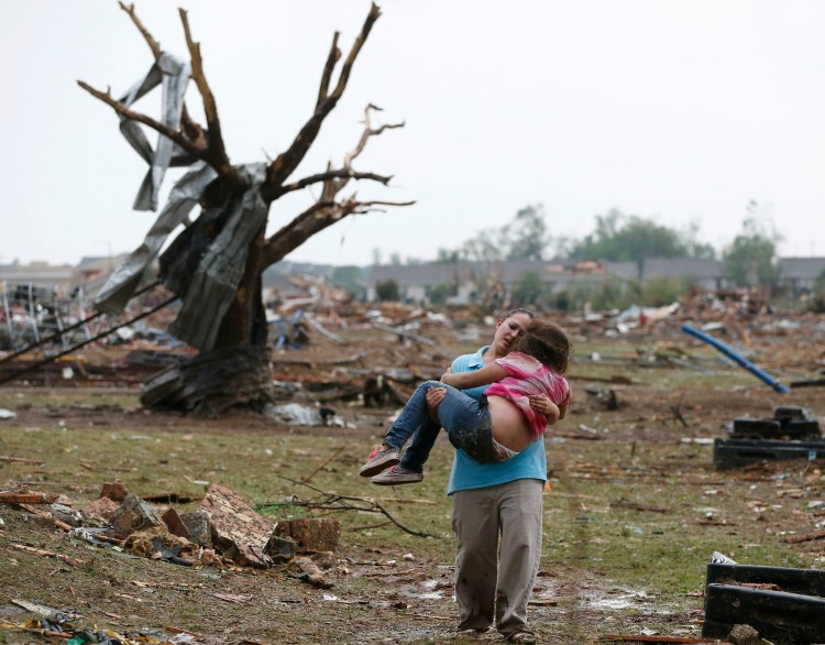 In this May 20, 2013, file photo, LaTisha Garcia carries her 8-year-old daughter, Jazmin Rodriguez, near Plaza Towers Elementary School after a massive tornado carved its way through Moore, Okla., leaving little of the school and neighborhood. Photo credit: AP Photo/Sue Ogrocki, File