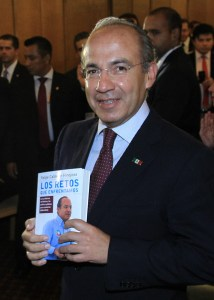 Mexico's president  from 2006 to 2012, Felipe Calderon poses with a book about his government work, in Mexico City, Aug. 13, 2014. (EPA/Mario Guzman)