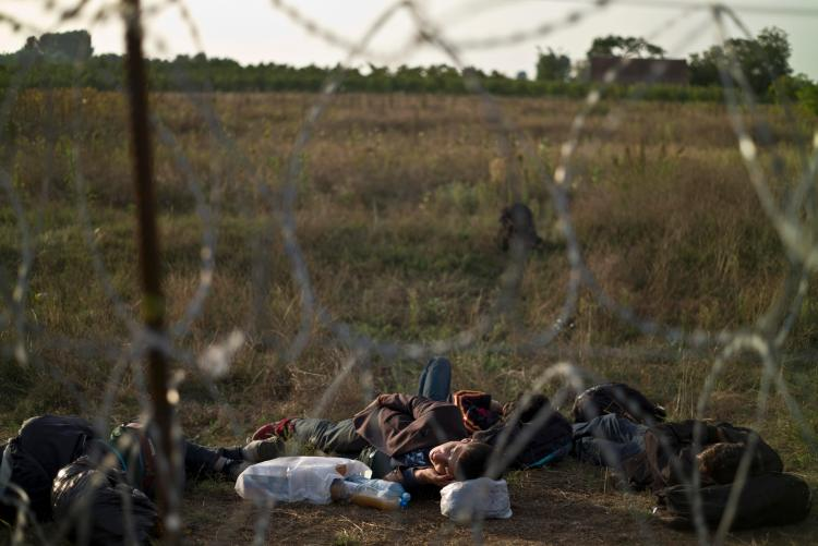 Afghan refugees sleep next to razor-wire barrier at the Serbian side of Hungary's border fence with Serbia, in Asotthalom, southern Hungary, Sept. 17, 2015. (AP Photo/Muhammed Muheisen)