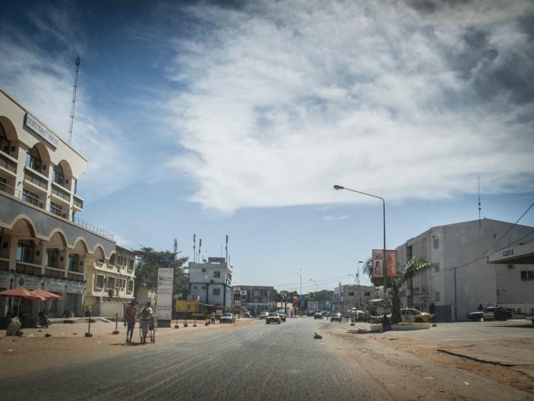 Residents walk on an empty street in Banjul Gambia, Dec. 30, 2014. (AP Photo/Jason Florio)