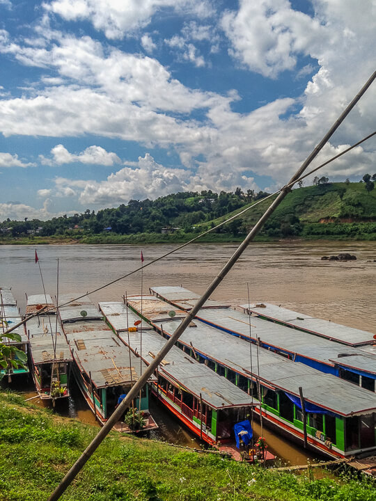 long wooden boats travel mekong river laos
