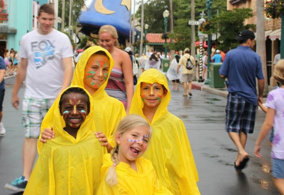 Transracial adoptive family in ponchos at Disneyworld