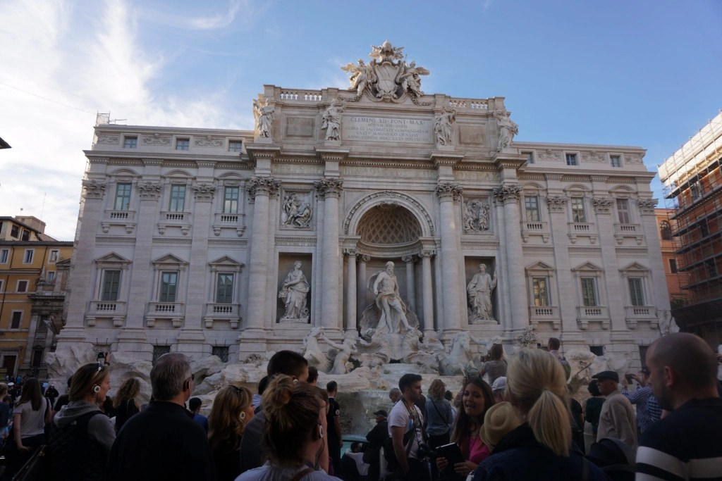 A straight shot of Trevi Fountain with tourists all around it- Global Munchkins