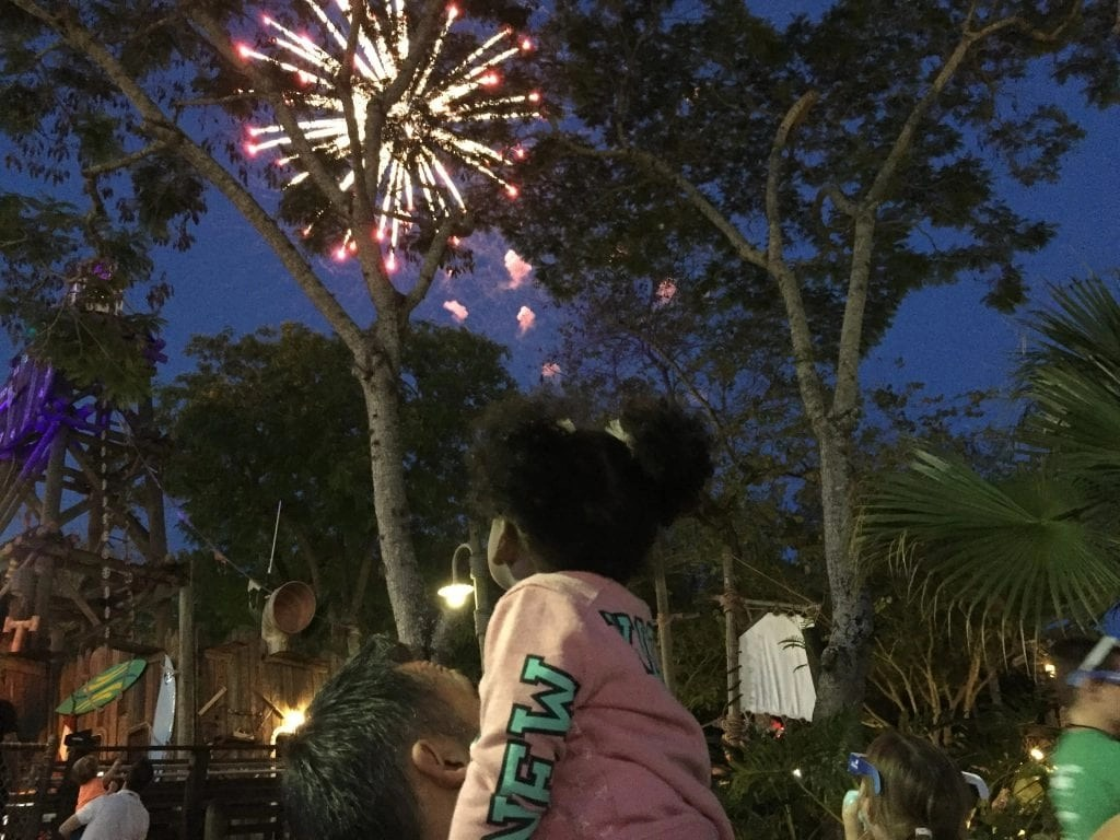 Little girl on dad's shoulders watching Disney Fireworks | Global Munchkins