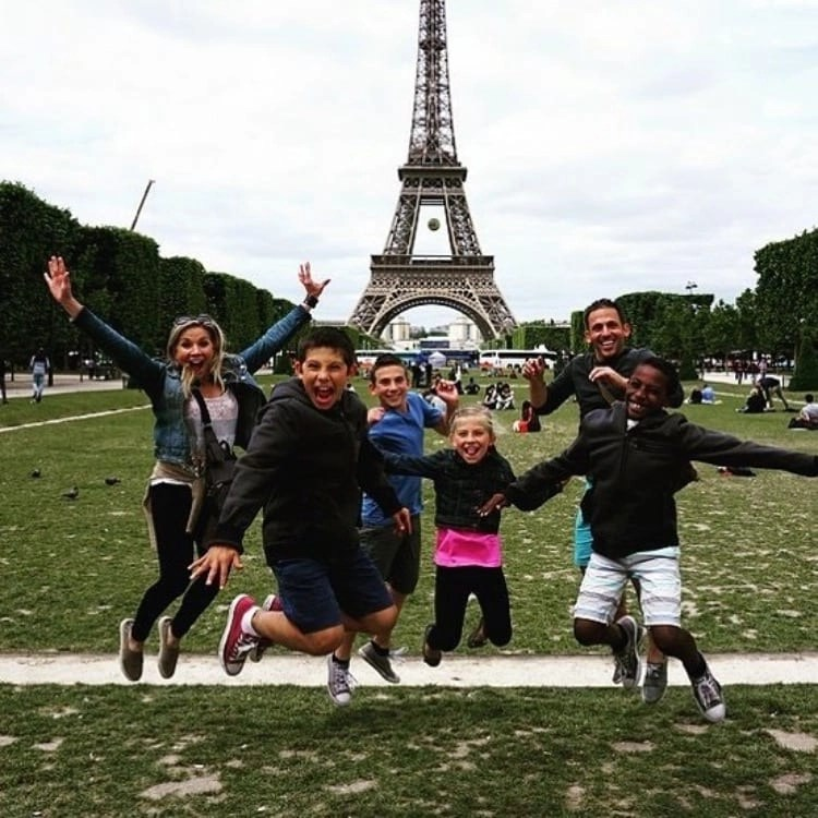 Family jumping for joy in front of the Eiffel Tower in Paris France