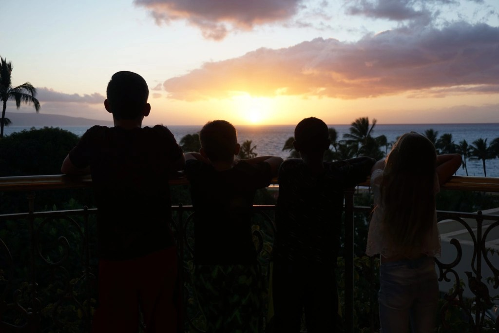 Silhouettes of kids watching sunset on balcony at Grand Wailea in Maui Hawaii