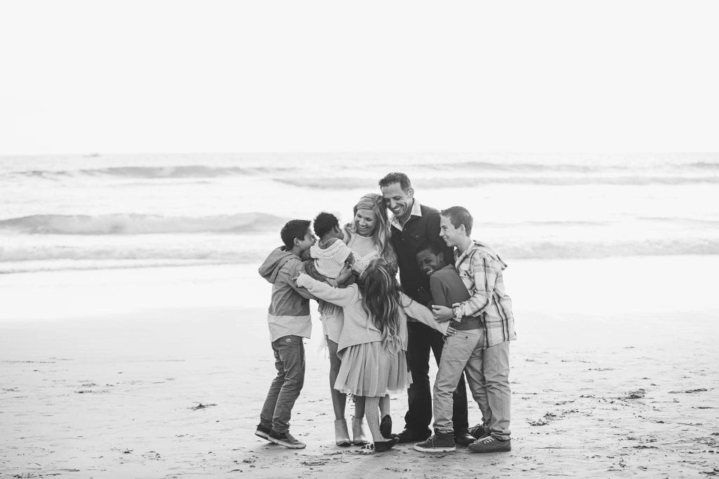 Family huddling together and embracing on a beach | Global Munchkins