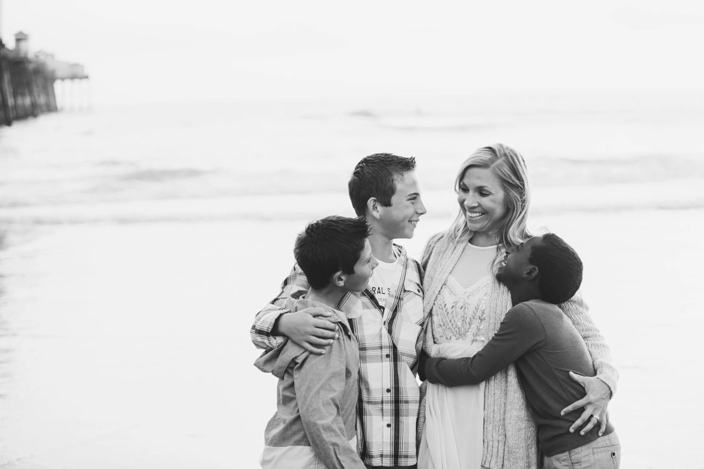 """Being """"mom enough"""" A black and white photo of a mother embracing her adopted and biological sons on a beach 