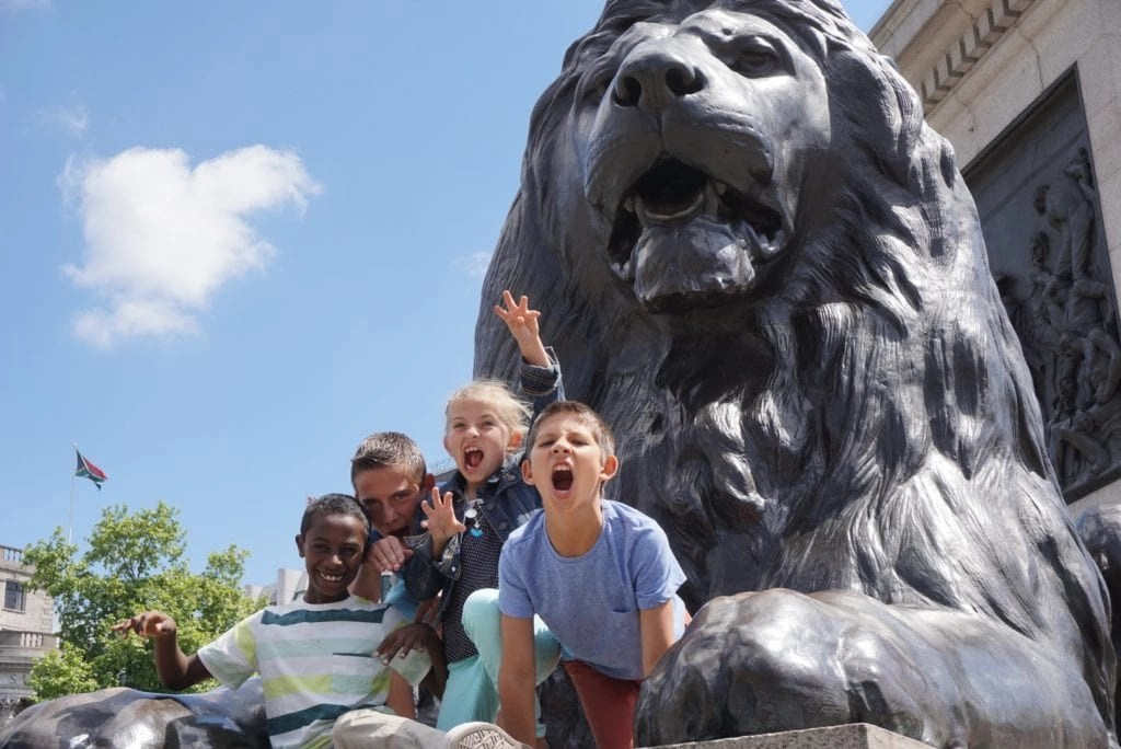 Kids growling on the Lions statues in Trafalgar Square | London with Kids | Global Munchkins