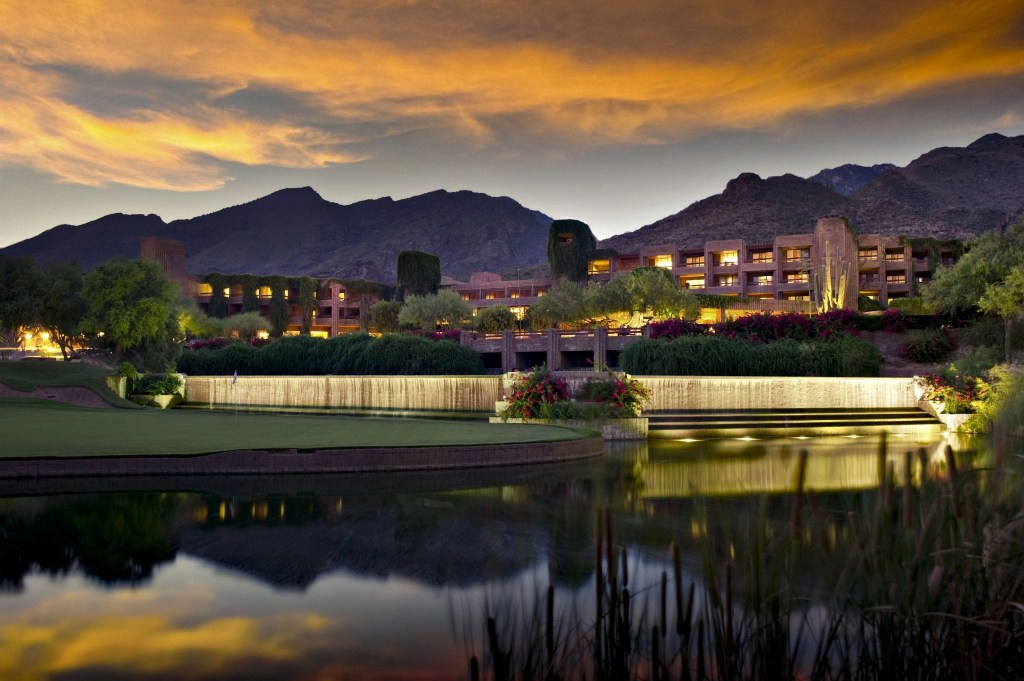 Long exposure of a luxury hotel resort. A golf course and pond is in the foreground and foothill mountians in the background.