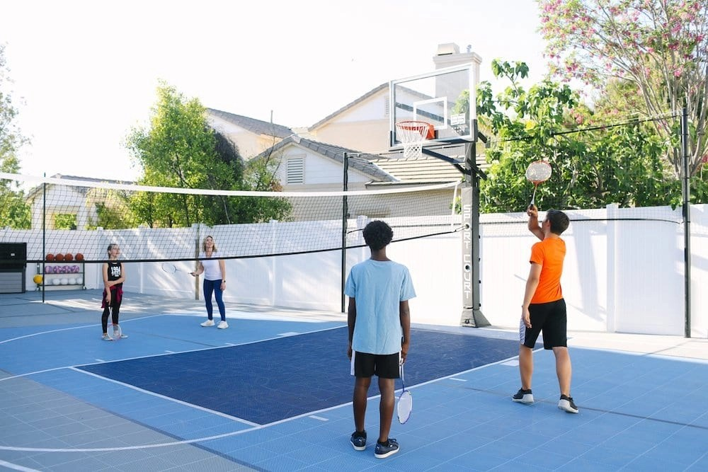 Our backyard court from Sport Court is a Multi-Game Court featuring Basketball, Badminton, Pickleball, Volleyball, Tetherball, and Four Square. It's incredibly versatile.