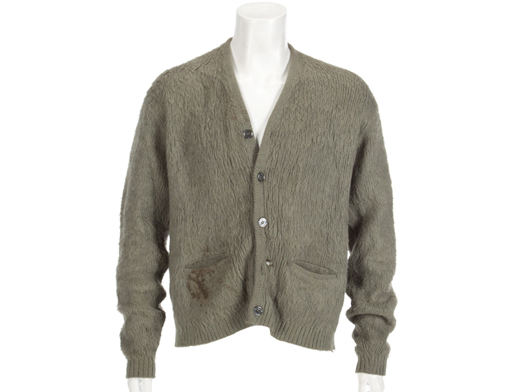 This image released by Julien's Auctions shows an olive green cardigan sweater worn by Nirvana frontman Kurt Cobain during Nirvana's MTV's 'Unplugged' performance. The sweater, along with Cobain's custom Fender guitar, were among many rock and roll items up for auction on Oct. 25 and 26.