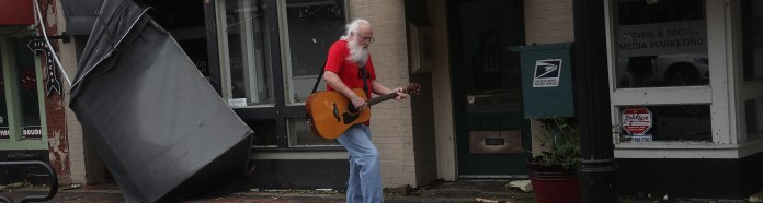 Mitch Pickering plays his guitar as he walks downtown after Hurricane Laura hits August 27, 2020 in Lake Charles, Louisiana.