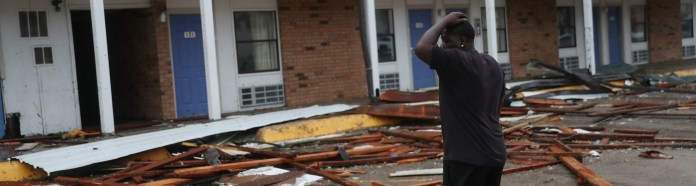 A person stands next to a hotel with parts of its roof ripped off when Hurricane Laura swept through the region on August 27, 2020 in Lake Charles, Louisiana.