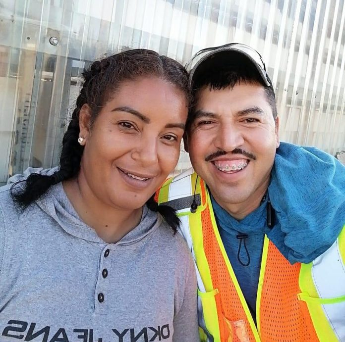 Erika Zavala (left) and Jesús Molina take a photo together at Bylands, the BC farm that fired them in July for inviting two people to the property.  Bylands told Global News that this violated its policy regarding