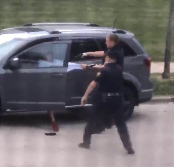 A police officer pulls on Jacob Blake's shirt, moments before shooting him on Aug. 23, 2020, in Kenosha, Wisc.