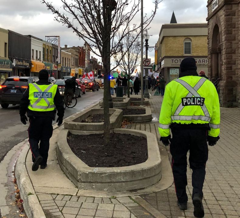 Woodstock police officers tail a march down Dundas Street following a rally against COVID-19 health measures.