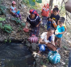 Women and children collect water from a river