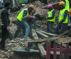 Emergency workers and bystanders clear debris while searching for survivors under a collapsed temple in Basantapur Durbar Square following an earthquake on April 25, 2015 in Kathmandu, Nepal. A major 7.8