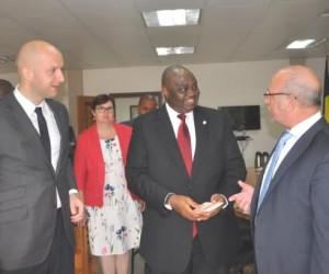 . Lamorde hands the money to Ambasador De Loecker