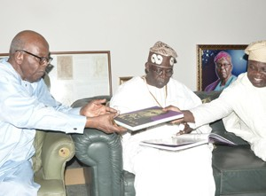 Lagos State Governor, Mr. Akinwunmi Ambode (right) handing a book to Afenifere Leader, Pa Olaniwun Ajayi while National Leader, All Progressives Congress (APC), Asiwaju Bola Tinubu watches during a courtesy visit to Pa Olaniwun at his Ijebu-Ishara residence in Ogun State, recently.