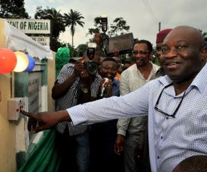 Abia state Governor, Dr. Okezie Ikpeazu switching on the light to officially inaugurate the Electricity Project for Ibeme Oberete Isiala Autonomous Community in Obingwa LGA. With him is Hon. Emeka Stanley, Chairman ASOPADEC and other top state functionaries.