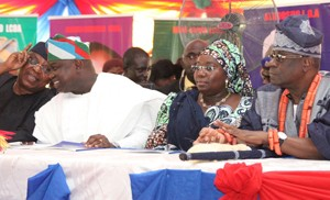 (R-L): Lagos State Governor, Mr. Akinwunmi Ambode (2nd left) discussing with the State Chairman, All Progressives Congress (APC), Otunba Henry Ajomale during the maiden edition of the Quarterly Town Hall meeting to render account of stewardship of Governor Ambode's administration 1st quarter in Office, at the Abesan Mini Stadium, Abesan Housing Estate, Ipaja, Lagos, on Tuesday, October 06, 2015. With them are Deputy Governor, Dr.(Mrs.) Oluranti Adebule (2ndright) and Oba of Lagos, Oba Rilwan Akiolu I (right).