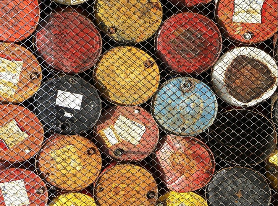 Stacked barrels of oil behind a chainlink fence