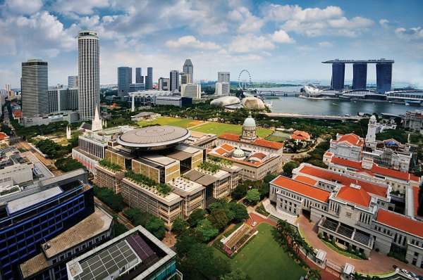 An aerial view of the Civic District of Singapore. The buildings visible include the Supreme Court of Singapore (centre left, with disc), the Old Supreme Court Building (centre right, with dome), and Parliament House (right, with orange roof). In the background are the three towers of the Marina Bay Sands Hotel. Photo by William Cho.