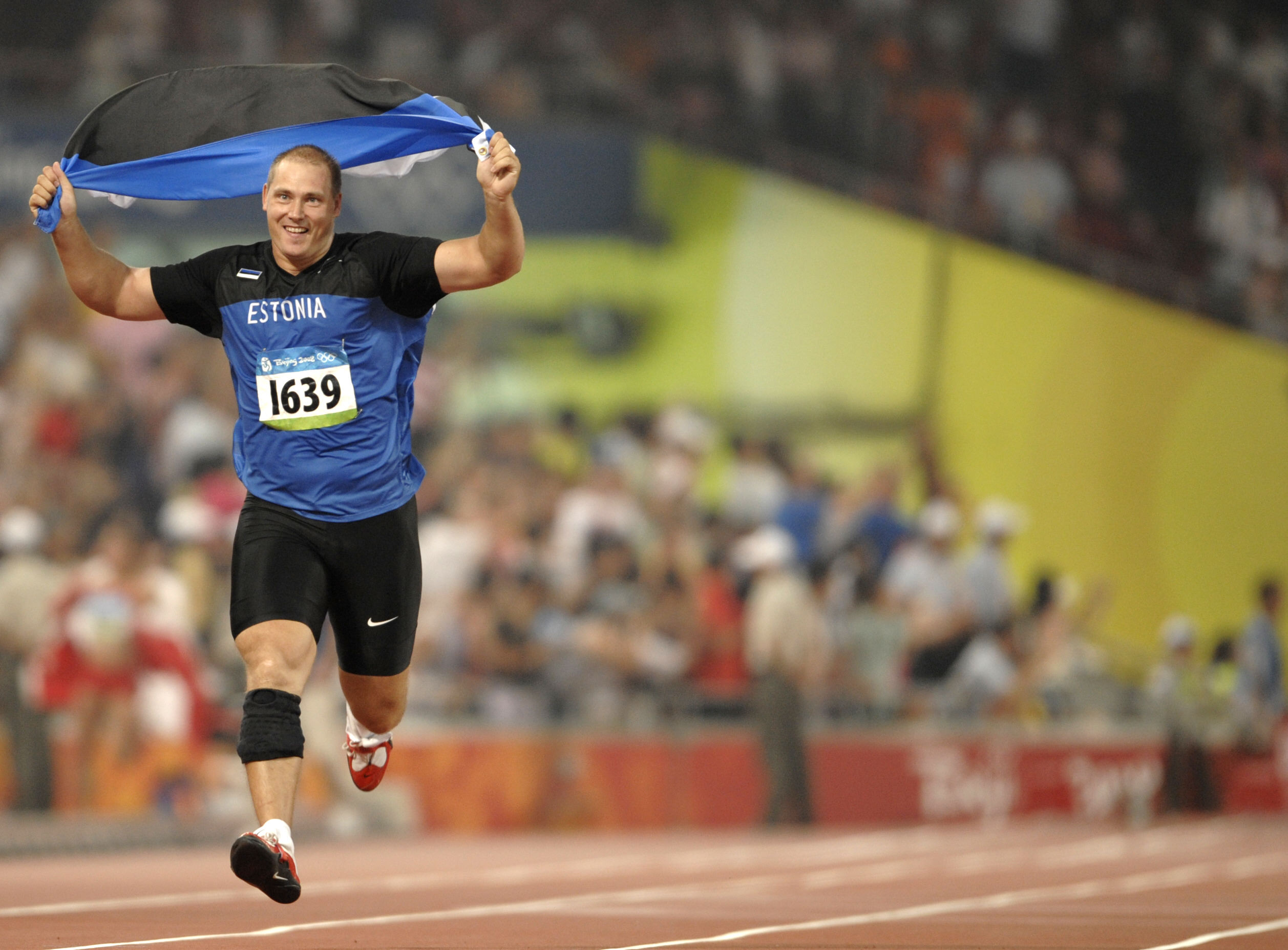 Discus Thrower Gerd Kanter performs a victory lap after clinching the Olympic title in 2008