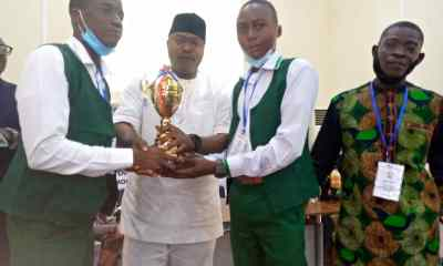 The FCT branch II ANAN chairman, Mr Emmanuel Abgo, present a trophy to students