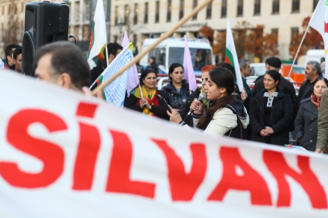 Berlin, Germany. 12th November 2015 -- A woman gives a speech behind a banner remembering Silvan. -- Dozens Kurds and Yazidi rally at Berlin's Brandenburg Gate to condemn Turkish attacks on and the siege of Kurdish Silvan in Turkey. They also remember the fate of the Yazidi in Iraq who are murdered and enslaved by the Islamic State (ISIS) .
