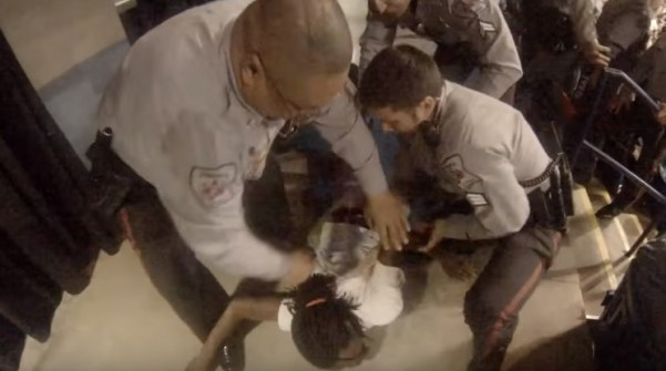A screenshot of footage, uploaded to YouTube by Storyful, of a protester who was assaulted by a Donald Trump supporter being restrained by police at a rally in North Carolina.