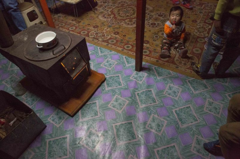 Eight month-old Munkh-erdene sits next to his family's traditional stove in thier ger, or yurt in Ulaanbaatar. The stoves are meant to burn wood or animal dung, but many families use them to burn coal, causing a spike in air pollution in the winter. Credit: Anne Bailey