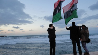 Libyans waving their flag by the sea