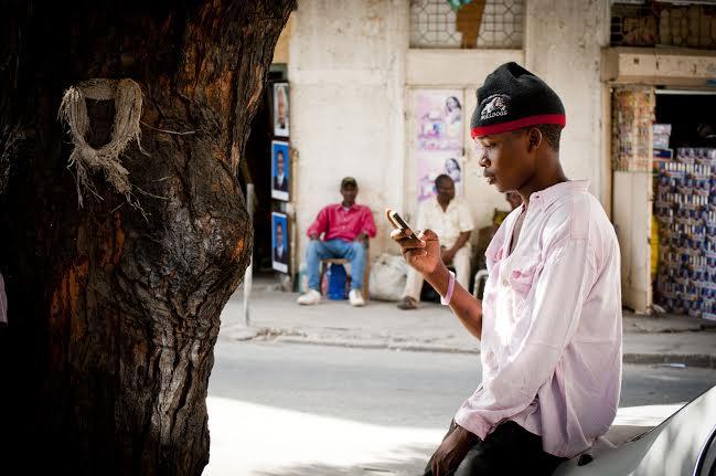 Un jeune homme envoyant des textos sur son téléphone portable à Dar Es Salaam, en Tanzanie. Photo par Pernille Baerendtsen, utilisée avec permission.